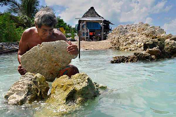 Albert Ientau rebuilds his sea wall to protect his home in the village of Abarao on the island of Tarawa. Photo by Justin McManus, The Age