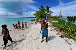 Residents stand by the site of their former village, Tebunginako, now inundated by the sea.  Photo: Justin McManus/The Age.