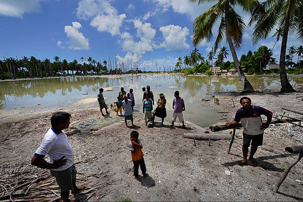 nginako villagers standing the sea where their village used to be had to relocate their village because of rising seas and erosion.  Photo:Justin McManus, The Age