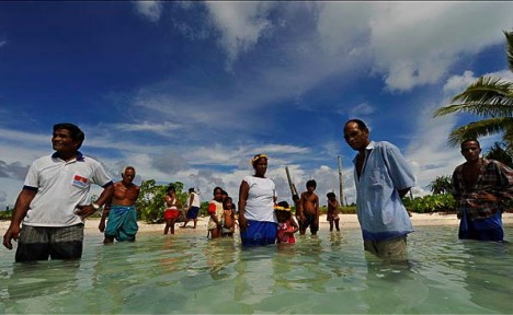 Tebunginako villagers stand in the sea where their village used to be. They had to relocate their village because of rising sea levels, erosion and saltwater inundation. Photo: Justin McManus, The Age