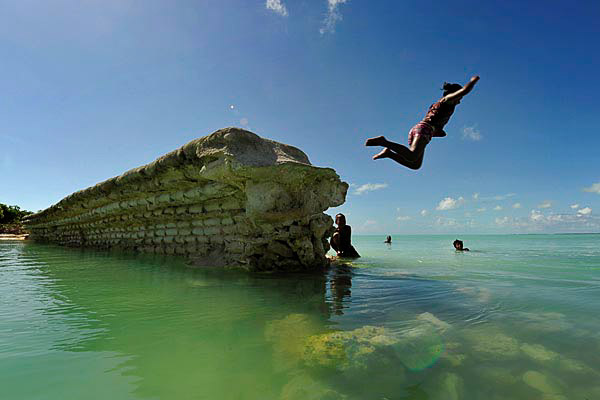 Kid jumping off a sea wall in the village of Eita  on the island of Tarawa. Photo: Justin McManus, The Age