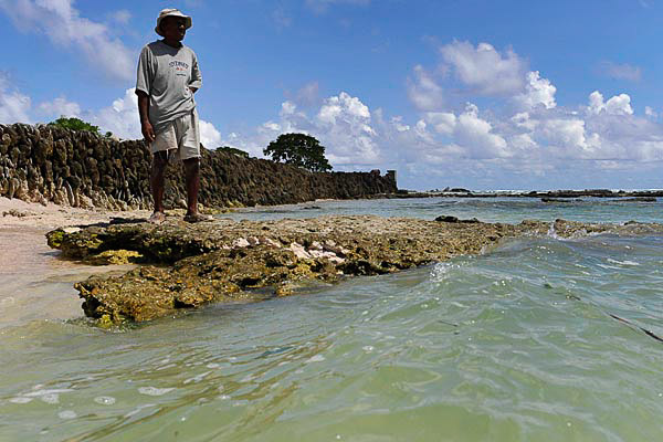 Kirarenti Muller in front of the sea wall protecting his home in the village of Temwaiku on the island of Tarawa. Photo: Justin McManus, The Age