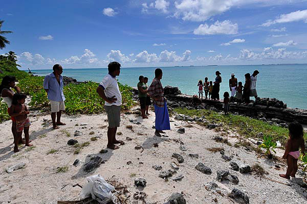 Tebunginako villagers stand in the sea where their village used to be. They had to relocate their village because of rising sea levels, erosion and saltwater inundation. Photo: Justin McManus/The Age