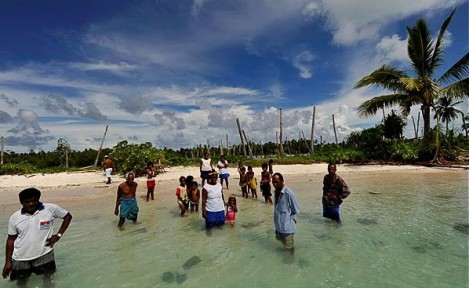 These Tebunginako villagers standing the sea where their village used to be had to relocate their village because of rising seas and erosion. Photo: Justin McManus, The Age