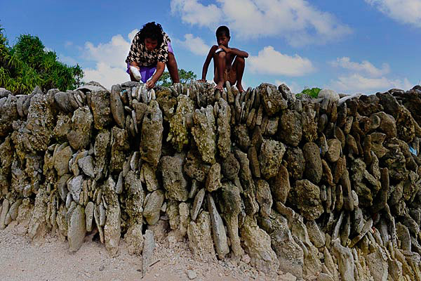 Totibure Muller and her son work on their sea wall that protects their home in the village of Temwaiku on the island of Tarawa. Photo: Justin McManus, The Age